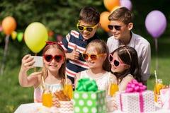 Enfants heureux prenant le selfie sur la fête d'anniversaire Images libres de droits