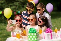 Enfants heureux prenant le selfie sur la fête d'anniversaire Photographie stock libre de droits