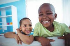 Enfants heureux regardant de derrière du divan Photo stock