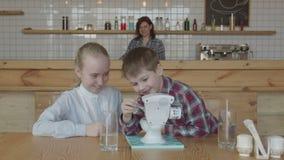 Enfants heureux riant jouant le jouet à la table de cafétéria banque de vidéos