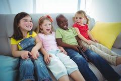 Enfants heureux riant tout en s'asseyant Photographie stock libre de droits