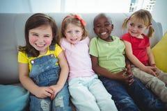 Enfants heureux riant tout en s'asseyant Photos libres de droits
