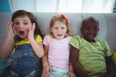 Enfants heureux riant tout en s'asseyant Image stock