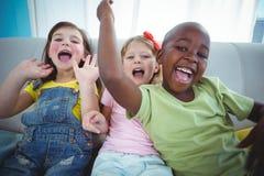 Enfants heureux riant tout en s'asseyant Images stock