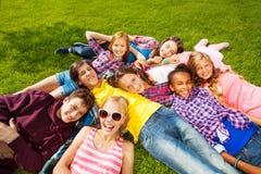 Enfants heureux s'étendant ensemble sur l'herbe verte Image libre de droits