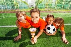 Enfants heureux s'étendant sur l'herbe avec le gobelet d'or Photographie stock libre de droits