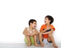 Enfants heureux s'asseyant à la maison Photographie stock