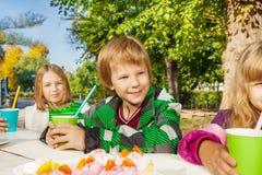 Enfants heureux s'asseyant à la table blanche en bois Photographie stock