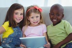 Enfants heureux s'asseyant ainsi qu'un comprimé Image stock