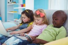 Enfants heureux s'asseyant ainsi qu'un comprimé et un ordinateur portable et un téléphone Photos libres de droits