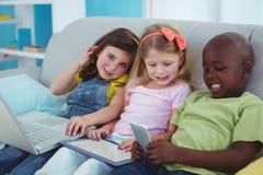 Enfants heureux s'asseyant ainsi qu'un comprimé et un ordinateur portable et un téléphone Photo libre de droits
