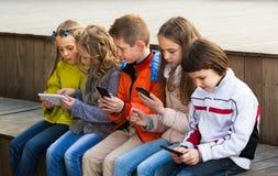 Enfants heureux s'asseyant avec des périphériques mobiles Photos stock