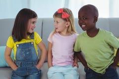 Enfants heureux s'asseyant ensemble Photographie stock