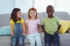 Enfants heureux s'asseyant ensemble Photo stock