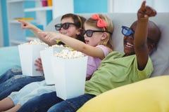 Enfants heureux s'asseyant ensemble observant un film Photographie stock libre de droits