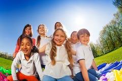 Enfants heureux s'asseyant ensemble sur la pelouse au jour ensoleillé Image stock