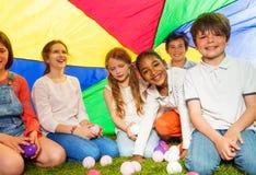 Enfants heureux s'asseyant sous l'auvent fait de parachute Photo stock