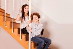 Enfants heureux s'asseyant sur l'escalier à l'intérieur Photo libre de droits