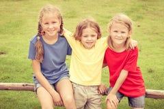 Enfants heureux s'asseyant sur l'herbe Photo stock
