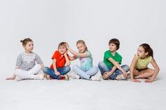 Enfants heureux s'asseyant sur le plancher au studio, l'espace de copie Photos libres de droits