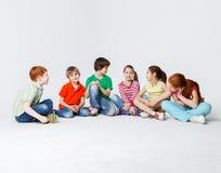 Enfants heureux s'asseyant sur le plancher au studio, l'espace de copie Image libre de droits