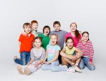 Enfants heureux s'asseyant sur le plancher au studio, l'espace de copie Photographie stock