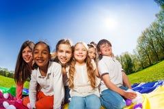 Enfants heureux s'asseyant sur le tapis coloré en parc Photo libre de droits