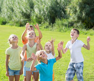 Enfants heureux sautant ensemble en parc l'été Photographie stock