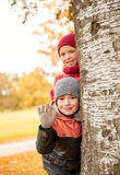 Enfants heureux se cachant derrière l'arbre et la main de ondulation Photographie stock libre de droits