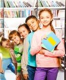 Enfants heureux se tenant dans la rangée à l'intérieur de la bibliothèque Photo libre de droits