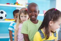 Enfants heureux se tenant dans une ligne Photographie stock