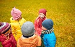 Enfants heureux se tenant en cercle au parc d'automne Images libres de droits