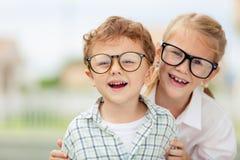 Enfants heureux se tenant sur la route au temps de jour Photos libres de droits