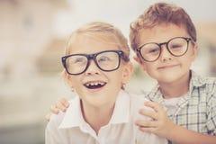 Enfants heureux se tenant sur la route au temps de jour Images stock