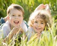 Enfants heureux se trouvant sur l'herbe Photographie stock