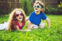 Enfants heureux se trouvant sur l'herbe Foyer sur une fille Photos stock