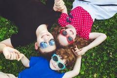 Enfants heureux se trouvant sur l'herbe tenant des mains Photographie stock libre de droits