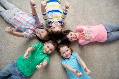 Enfants heureux se trouvant sur le plancher et montrant des pouces  Images stock