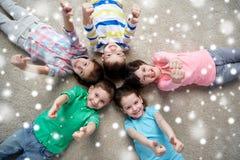 Enfants heureux se trouvant sur le plancher et montrant des pouces  Photo libre de droits