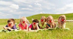 Enfants heureux se trouvant sur le pré au jour rouge de nez Images stock