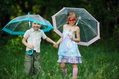 Enfants heureux sous le parapluie en parc Image stock