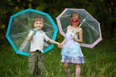 Enfants heureux sous le parapluie en parc Image libre de droits