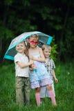 Enfants heureux sous le parapluie en parc Photos libres de droits