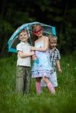 Enfants heureux sous le parapluie en parc Images libres de droits