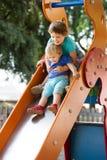 Enfants heureux sur la glissière Images libres de droits