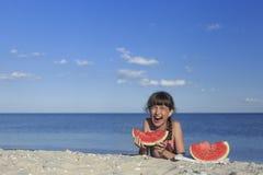 Enfants heureux sur la plage mangeant la pastèque douce Photo stock