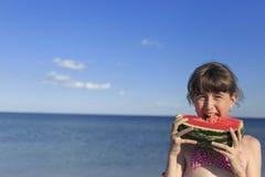 Enfants heureux sur la plage mangeant la pastèque douce Photos libres de droits
