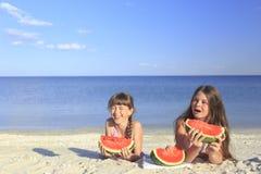 Enfants heureux sur la plage mangeant la pastèque douce Photographie stock