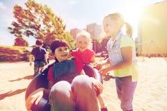 Enfants heureux sur le terrain de jeu d'enfants Photo stock