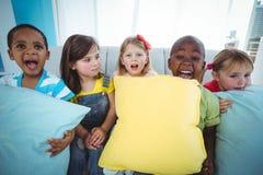Enfants heureux tenant des coussins de divan Photographie stock